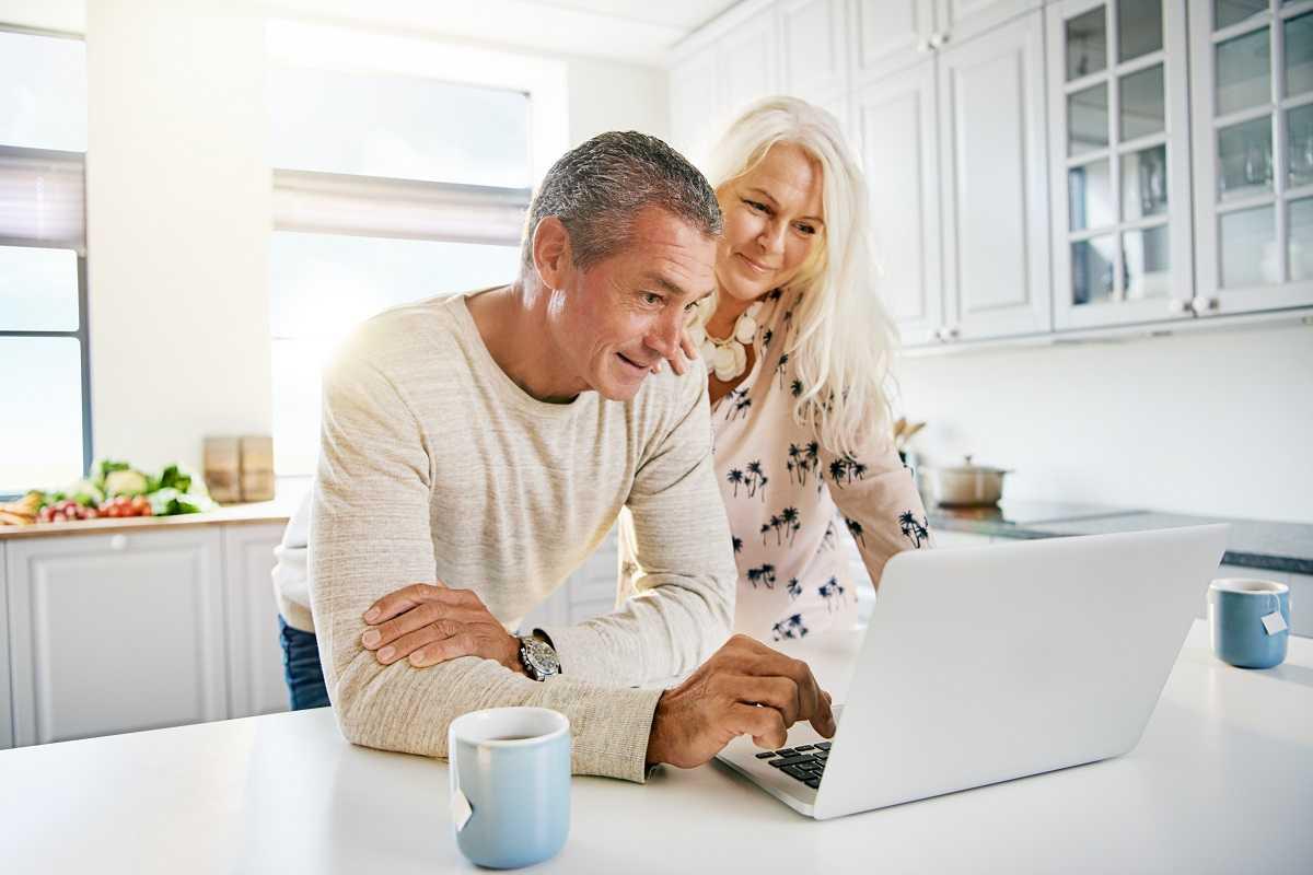 elderly-retired-couple-reading-their-social-media-PWCVTD8